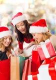 Jeunes femmes de sourire dans des chapeaux de Santa avec des cadeaux Photo libre de droits