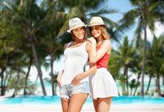 Jeunes femmes de sourire dans des chapeaux sur la plage Images libres de droits