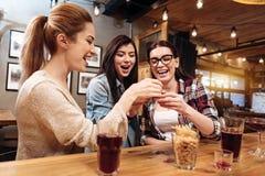 Jeunes femmes de sourire faisant tinter des verres Images libres de droits