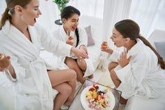 Jeunes femmes de sourire observant la réaction de fille à la bague de fiançailles image stock
