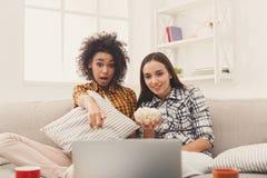 Jeunes femmes de sourire observant le film à la maison Photos libres de droits