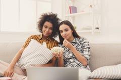 Jeunes femmes de sourire observant le film à la maison Photos stock
