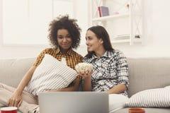 Jeunes femmes de sourire observant le film à la maison Photo libre de droits