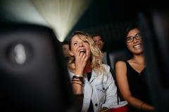 Jeunes femmes de sourire observant le film dans le théâtre Photo stock