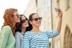Jeunes femmes de sourire prenant le selfie avec le smartphone Photos stock
