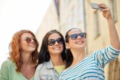 Jeunes femmes de sourire prenant le selfie avec le smartphone Photographie stock
