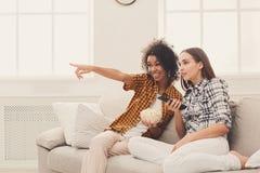 Jeunes femmes de sourire regardant la TV à la maison Photo libre de droits