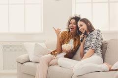 Jeunes femmes de sourire regardant la TV à la maison Photographie stock