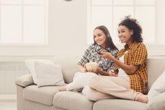 Jeunes femmes de sourire regardant la TV à la maison Image stock