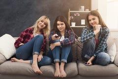 Jeunes femmes de sourire regardant la TV à la maison Photos stock