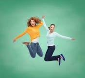 Jeunes femmes de sourire sautant en air Image libre de droits