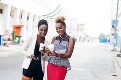 Jeunes femmes de sourire se tenant extérieures et tenir les téléphones intelligents Image stock