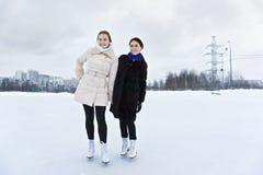 Jeunes femmes de sourire sur la patinoire Images stock