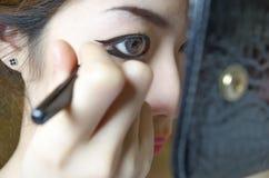 Jeunes femmes dessinant la doublure d'oeil Photos libres de droits