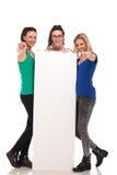 3 jeunes femmes dirigeant des doigts tout en tenant le grand conseil vide Photographie stock libre de droits