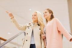 Jeunes femmes dirigeant le doigt sur l'escalator dans le mail Image libre de droits