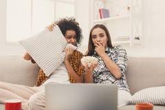 Jeunes femmes effrayées observant le film à la maison Photos stock