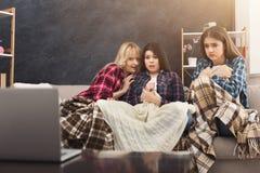 Jeunes femmes effrayées observant le film à la maison Images stock
