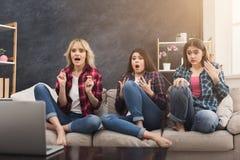 Jeunes femmes effrayées observant le film à la maison Photo libre de droits