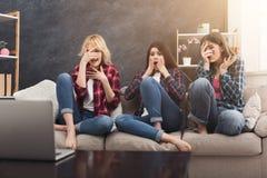Jeunes femmes effrayées observant le film à la maison Image stock