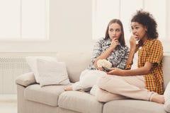 Jeunes femmes effrayées regardant la TV à la maison Images stock