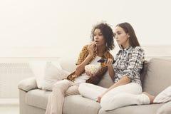 Jeunes femmes effrayées regardant la TV à la maison Photographie stock