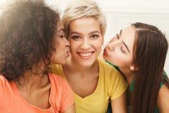 Jeunes femmes embrassant leur ami sur les joues Images stock