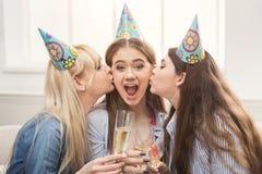 Jeunes femmes embrassant son ami sur les joues Photographie stock libre de droits