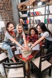 Jeunes femmes empilant des mains sur la pile des livres Image libre de droits