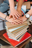 Jeunes femmes empilant des mains sur la pile des livres Image stock