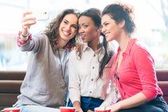 Jeunes femmes en café prenant le selfie Photo libre de droits