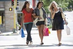 Jeunes femmes en voyage d'achats texting Photos stock