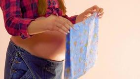 Jeunes femmes enceintes pr?parant les v?tements s'enveloppants pour la naissance du b?b? Concept de grossesse et de maternit? Tir banque de vidéos