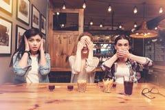 Jeunes femmes espiègles couvrant leurs visages Image libre de droits