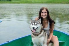 Jeunes femmes et son costaud de chien se reposant près du lac en été Photos stock