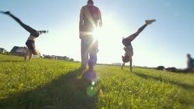 Jeunes femmes exécutant la roue acrobatique sur l'herbe, silhouette de jeune homme se tenant au centre de eux banque de vidéos