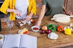 Jeunes femmes faisant cuire la pizza tout en se tenant ensemble à la table de cuisine avec le livre de cuisine vide Photo stock