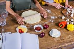 Jeunes femmes faisant cuire la pizza tout en se tenant ensemble à la table de cuisine avec le livre de cuisine vide Photo libre de droits