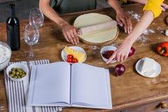 Jeunes femmes faisant cuire la pizza tout en se tenant ensemble à la table de cuisine avec le livre de cuisine vide Image stock
