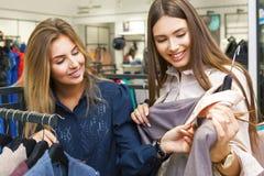 Jeunes femmes faisant des emplettes et regardant de l'habillement dans un magasin Photos stock
