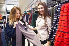 Jeunes femmes faisant des emplettes et regardant de l'habillement dans un magasin Photographie stock libre de droits