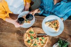 Jeunes femmes faisant tinter des verres de vin tout en mangeant de la pizza faite maison ensemble Images libres de droits