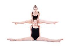 2 jeunes femmes flexibles de bel athlète situant dans la fente une sur des épaules des autres Photo libre de droits