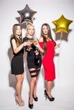 Jeunes femmes gaies buvant du champagne, parlant et riant avec des ballons sur la partie Images stock