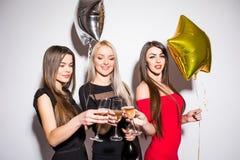 Jeunes femmes gaies buvant du champagne, parlant et riant avec des ballons sur la partie Image libre de droits