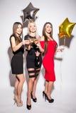Jeunes femmes gaies buvant du champagne, parlant et riant avec des ballons sur la partie Photo stock