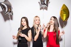 Jeunes femmes gaies buvant du champagne, parlant et riant avec des ballons sur la partie Image stock
