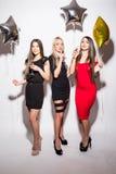 Jeunes femmes gaies buvant du champagne, parlant et riant avec des ballons sur la partie Photos libres de droits