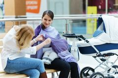 Jeunes femmes gaies européennes de couples ou d'amis avec le bébé s'asseyant sur un banc près de la voiture d'enfant blanche tand Image libre de droits