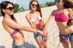 Jeunes femmes gaies se reposant sur la plage Image libre de droits